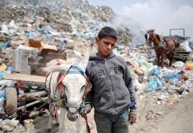 6 avril 2015, dans une décharge publique à Rafah, au sud de la bande de Gaza, un jeune palestinien de 14 ans fouille dans un tas de déchets à la recherche, entre autres, d'objets recyclables qu'il espère vendre (AFP / SAID KHATIB)