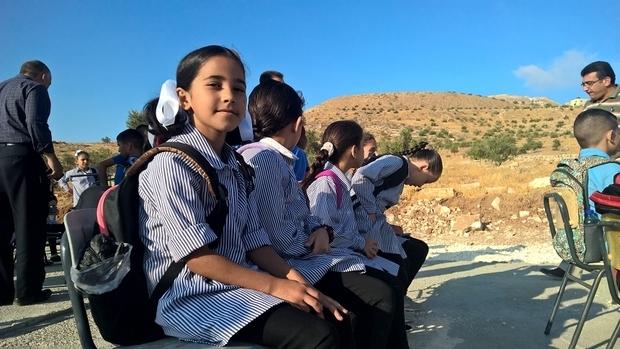 Des écoliers palestiniens sont assis patiemment pendant que des activistes installent une tente qui leur servira de classe (MEE/Chloé Benoist)
